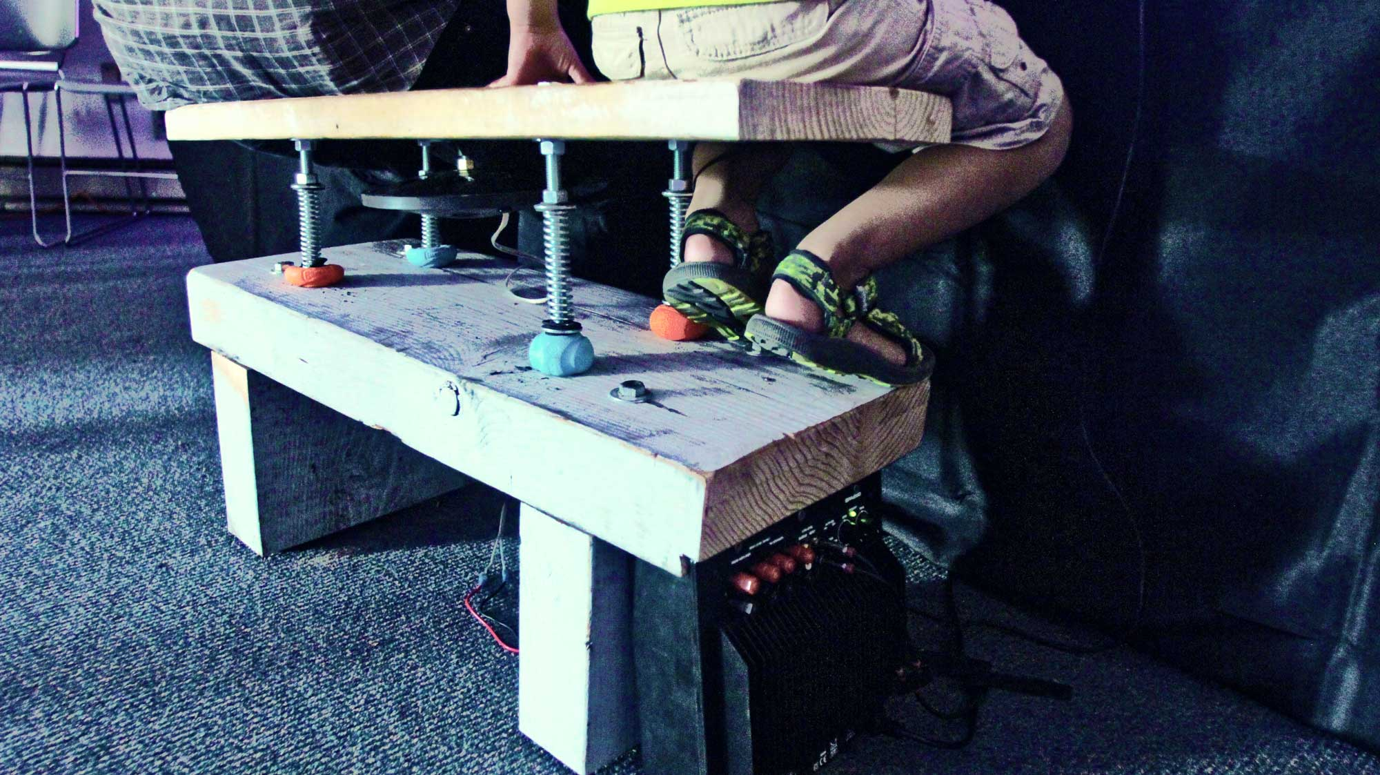 Two visitors sit on a vibro-haptic bench prototype designed at CymaSpace to feel sound and music via vibration and touch.